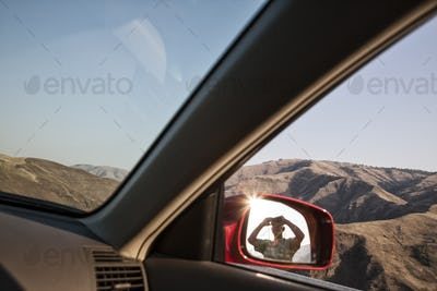 A person lookng through binoculars reflected in the side mirror of a car at a rest stop.