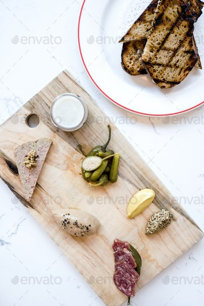 French charcuterie board with pickles, capers and mustard