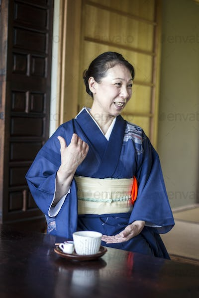 Smiling Japanese woman wearing blue kimono sitting on floor in traditional Japanese house.