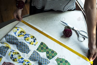 High angle close up of fashion designer working in studio, measuring piece of fabric.