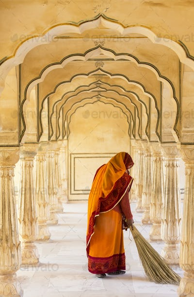 Rear view of woman wearing orange sari using broom to sweep floor of a colonnade.