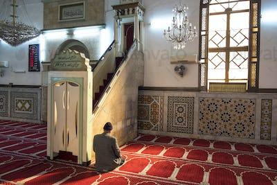 Rear view of man kneeling on floor in mosque, praying.
