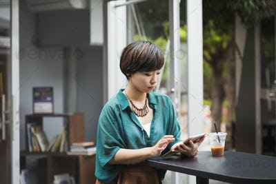 Woman with black hair wearing green shirt sitting at table in a street cafe, holding digital tablet.