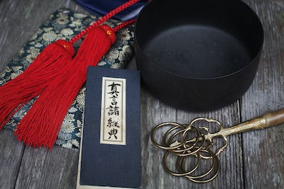 High angle close up of Buddhist prayer text, red silk tassel of a mala and black singing bowl.