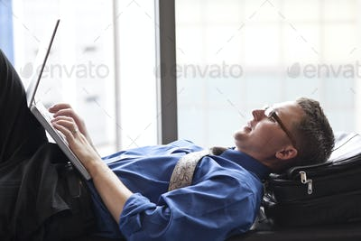 A businessman working on a laptop computer on a bench in a convention center lobby