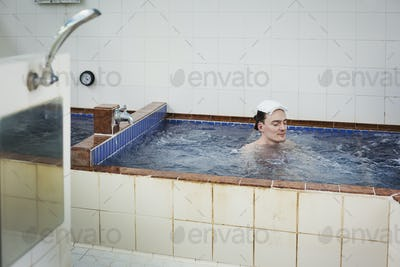 A man in a public bath house bath, in deep water with moving water jets, eyes closed.