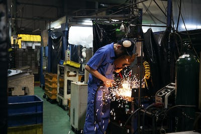Man wearing blue overall and welding mask standing in factory, welding metal, sparks flying.