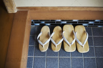 High angle view of two pairs of traditional Japanese sandals on a blue tiled floor.