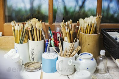 Close up of a selection of paintbrushes and tools in a Japanese porcelain workshop.