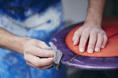 Man sanding and shaping a surfboard in a workshop