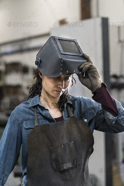 Portrait of woman wearing apron and welding mask standing in metal workshop.