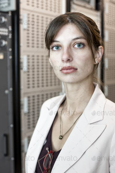 Portrait of female technician working in a large computer server room.