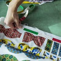 High angle close up of fashion designer working in his studio, measuring fabric.