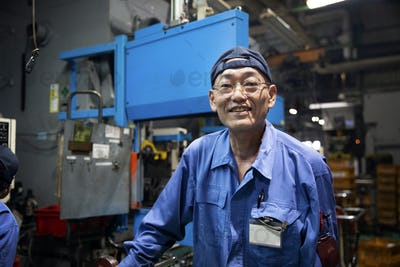 Japanese man wearing glasses and blue overall standing in factory, smiling at camera.