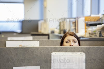 A young Caucasian woman looking concerned over the top of her cubicle in a corporate office.