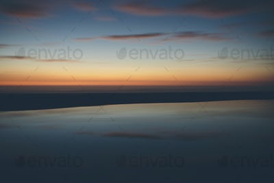 Seascape with cloudy sky at sunset.