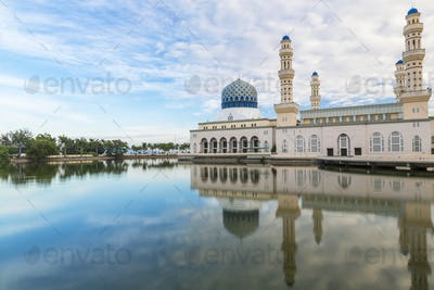 Exterior view of mosque with white washed facade and blue dome reflected in a pond.
