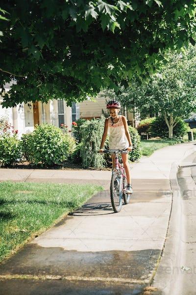 Tween Girl Biking on Sidewalk in Residential Neighborhood