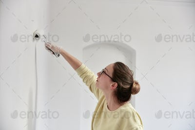 Woman reaching up using roller to paint wall
