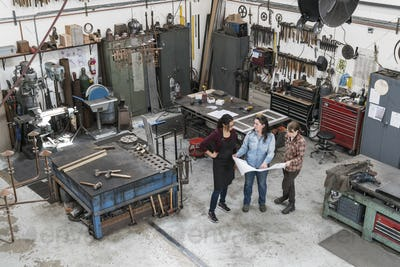 High angle view of three women standing in metal workshop, holding technical blueprint.