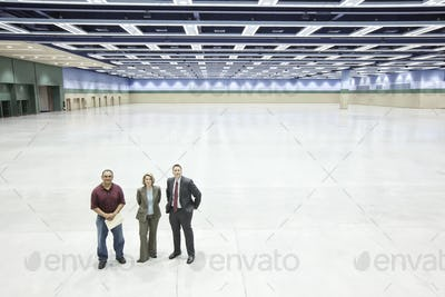 Three business meeting planners standing in the middle of a convention center arena.