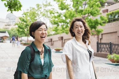 Two women with black hair wearing white and green shirt walking along street, smiling.