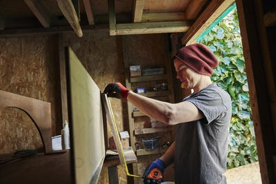 Carpenter using tape measure in shed