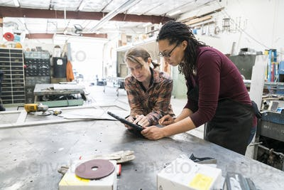 Two women standing at workbench in metal workshop, looking at digital tablet.