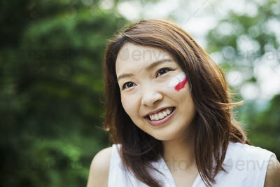 Portrait of young woman with brown hair, Japanese flag painted on her cheek, smiling at camera.