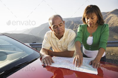 An Hispanic senior couple checking a paper map while pulled over at rest stop on a road trip.