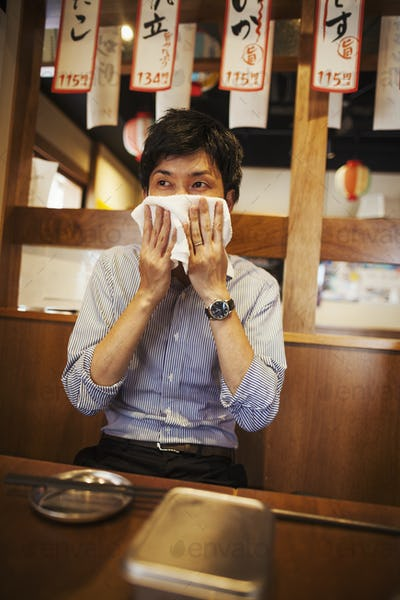Man sitting at a table in a restaurant, wiping his face with wet towel.