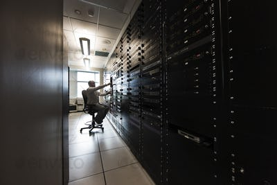 Computer server room racks with technician in background.