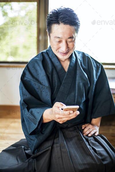 Japanese man wearing kimono sitting on floor in traditional Japanese house, using mobile phone.