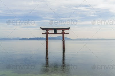 Tall red lacquered Torii gate in the middle of a lake.