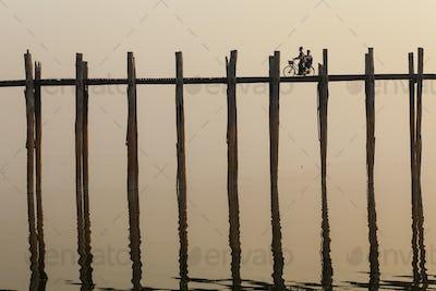 Two people cycling across tall teak bridge over a lake.