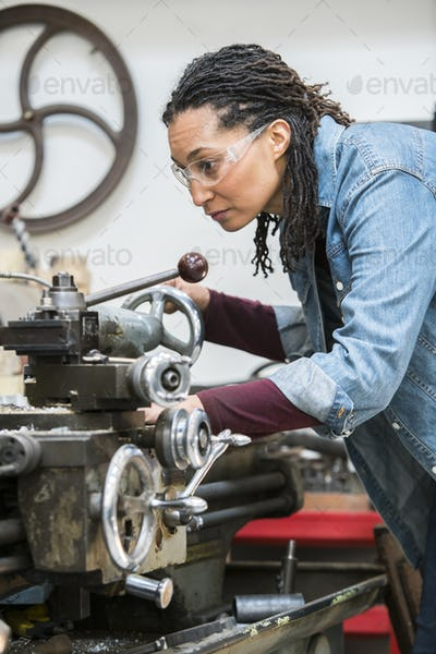 Woman wearing safety glasses standing in a metal workshop, working at metal lathe machine.