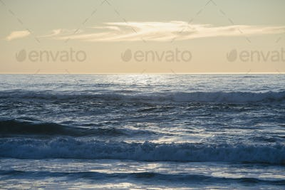 Seascape with breaking waves under cloudy sky at sunset.