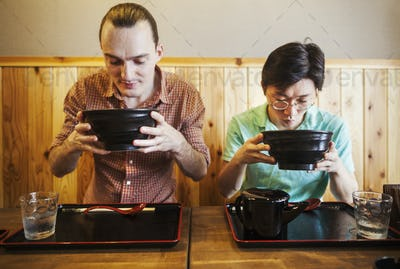 Two people in a noodle cafe lifting bowls of soba noodles. A western man and a Japanese man.