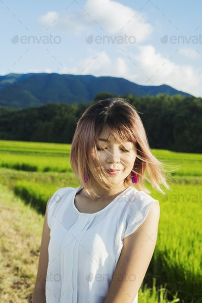 A young woman in a white shirt, hair blown in the wind, standing in open space by rice paddy fields.