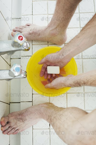 A man standing in a shower with soap in his hands, washing.