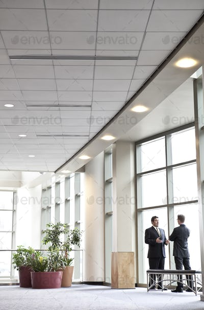 Two businessmen meeting in front of a window in a large convention center lobby.