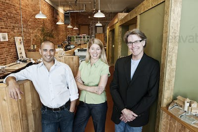 Portrait of a multi-ethnic team of three architects in a small office.
