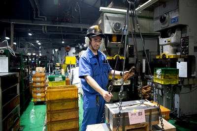 Japanese man wearing safety helmet, ear protectors and blue overall standing in factory, working.