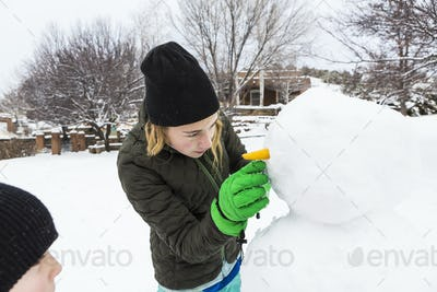 Teenage girl and her younger brother building a snowman in a garden