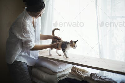 Woman indoors, holding calico cat with white, black and brown fur walking along a shelf.