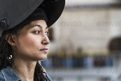 Portrait of woman wearing welding mask standing in metal workshop.