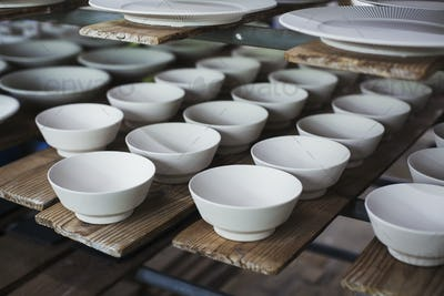 High angle close up of white bowls and plates in a Japanese porcelain workshop.