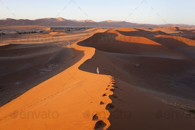 Aerial view of desert landscape, distant view of person walking along ridge of sand dune.