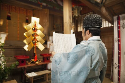 Rear view of priest holding scroll at Shinto Sakurai Shrine, Fukuoka, Japan.