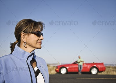 A portrait of a hip senior Hispanic woman on a road trip with her husband.